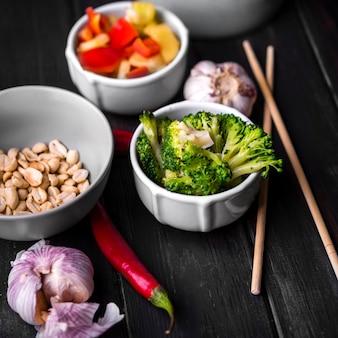 Close-up van groenten in kopjes met knoflook en eetstokjes