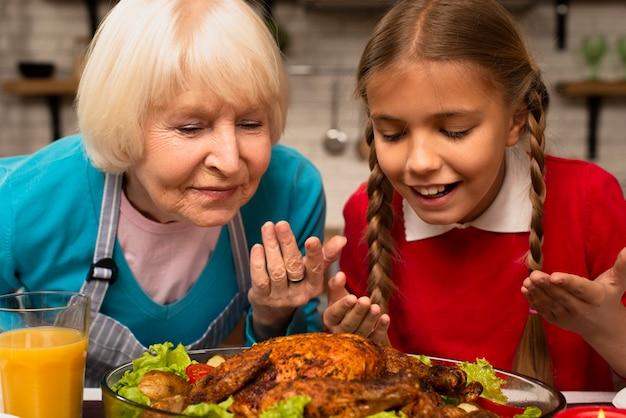 Close-up van grootmoeder en kleindochter die het voedsel ruiken