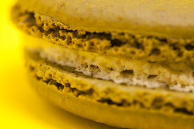 Close-up van grote macaroon kokos smaak op gele achtergrond.