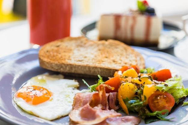 Close-up van half gebakken ei; spek; salade en toast op grijze keramische plaat