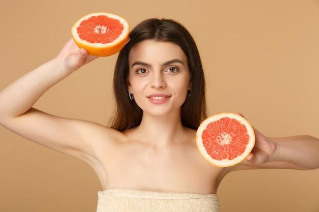 Close-up van halfnaakte vrouw met perfecte huid naakt make-up houdt grapefruit geïsoleerd op beige pastel muur