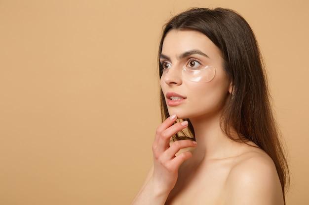 Close-up van halfnaakte vrouw met perfecte huid, naakt make-up patches onder ogen geïsoleerd op beige pastel muur