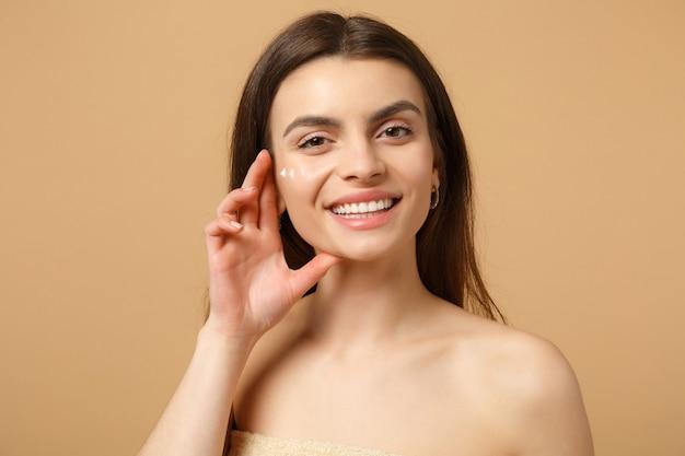 Close-up van halfnaakte vrouw met perfecte huid, naakte make-up, het aanbrengen van gezichtscrème geïsoleerd op beige pastelmuur