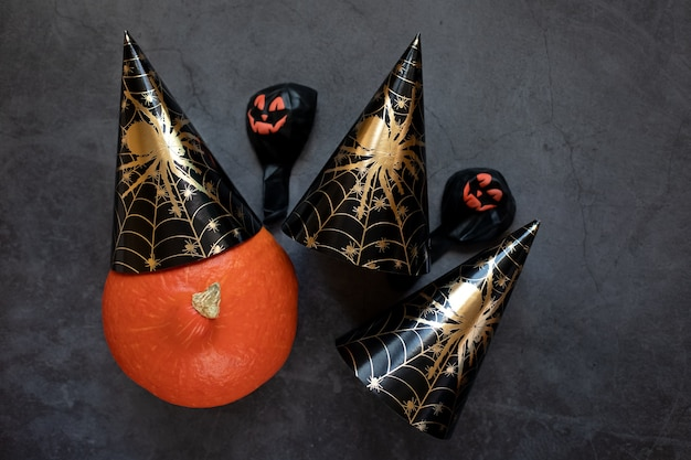 Close-up van halloween-pompoen in een zwarte papieren dop met een spin en ballen op een donkere achtergrond