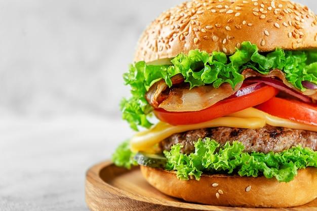 Close-up van hamburger met spek en kaas op grijze ondergrond