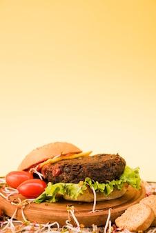 Close-up van hamburger met vrolijke tomaten; brood en sla op gele achtergrond