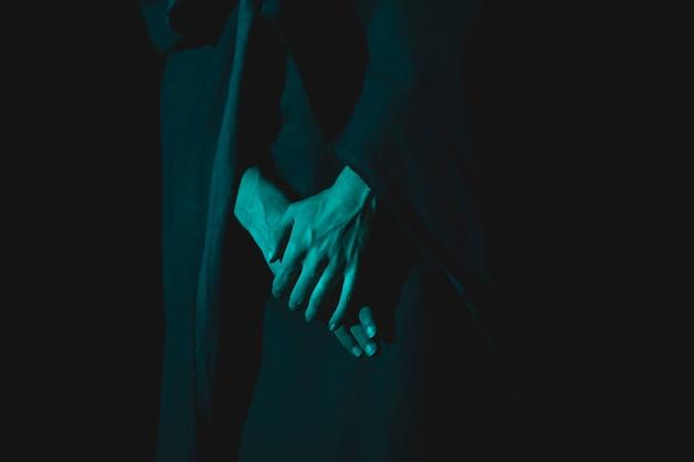 Close-up van hand die in de duisternis samenhoudt