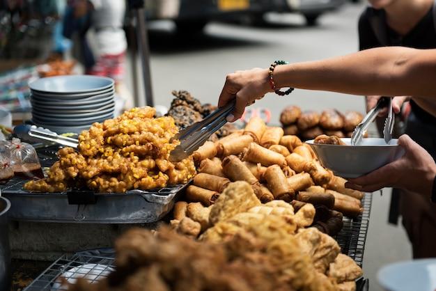 Close-up van hand die thais straatvoedsel opdracht geeft tot