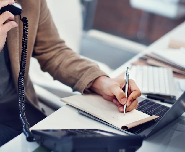 Close-up van hand het schrijven van nota terwijl op de telefoon