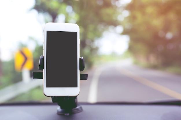 Close-up van hand houden met behulp van mobiele slimme telefoon met zwart scherm in auto console voorruit houder stok.