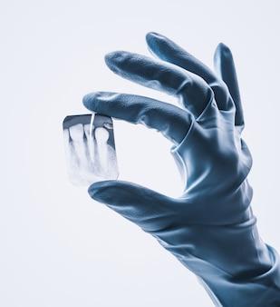 Close-up van hand in witte handschoen die kleine tandröntgenstraal houdt die op witte achtergrond wordt geïsoleerd