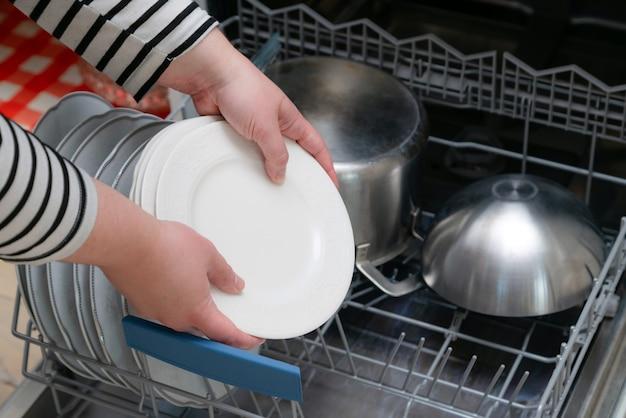Close up van hand lossen vaatwasser in de keuken. persoon die toestellen van volledige plank van vaatwasser neemt.