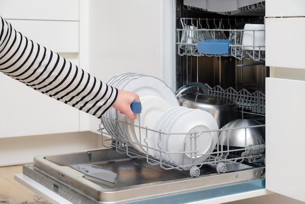 Close-up van hand lossen vaatwasser in de keuken.