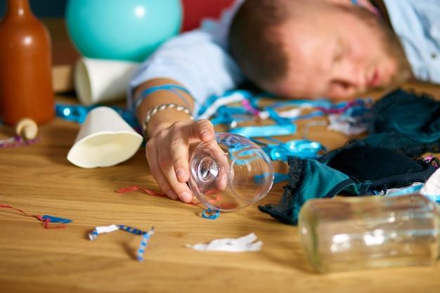 Close up van hand man houdt een glas cognac, slapen aan tafel in rommelige kamer na vrijgezellenfeest, moe man afterparty thuis