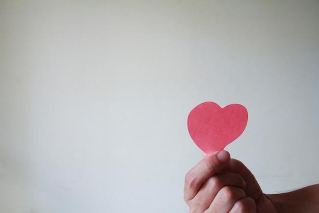 Close up van hand man met een papieren hart. liefdesconcept, gelukkige valentijn.