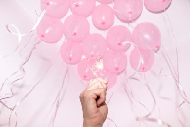 Close-up van hand met brandende sparkler onder het decoratieve plafond met roze ballonnen