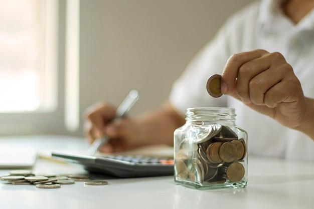 Close-up van hand munt aanbrengend een fles, geld te besparen, geldbesparende concept voor financiële boekhouding.