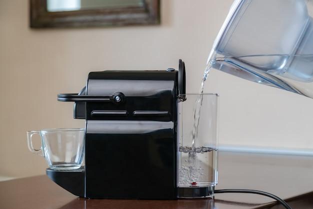 Close-up van hand puur gefilterd water gieten in capsule koffiemachine