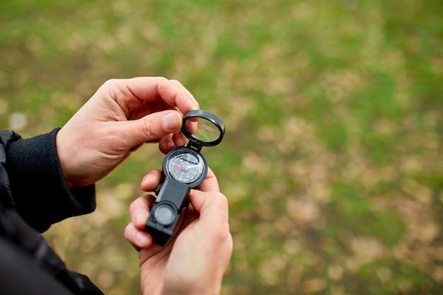 Close up van hand reiziger man met kompas op een achtergrond van bergen van de natuur