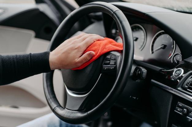 Close up van hand schoonmaak auto stuurwiel met microfiber doek