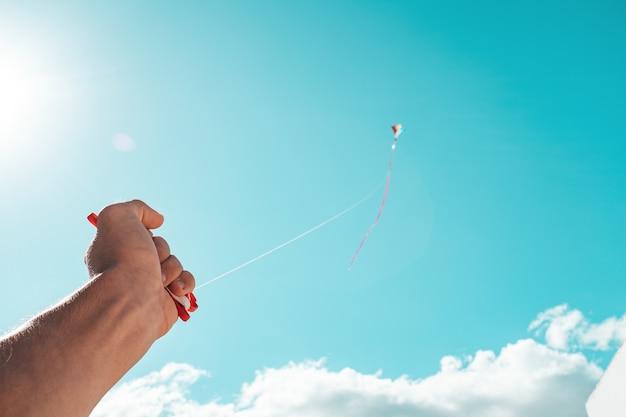 Close-up van hand vasthouden en spelen met een vliegende vlieger in de kleurrijke lucht