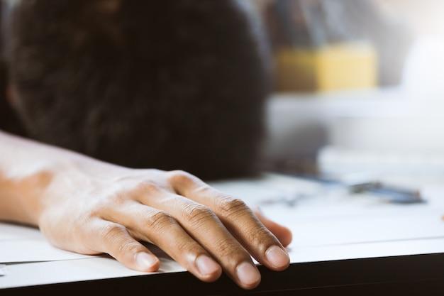 Close-up van hand zakenman met een dutje op bureau in werkruimte. concept bouwer werken aan huis project.