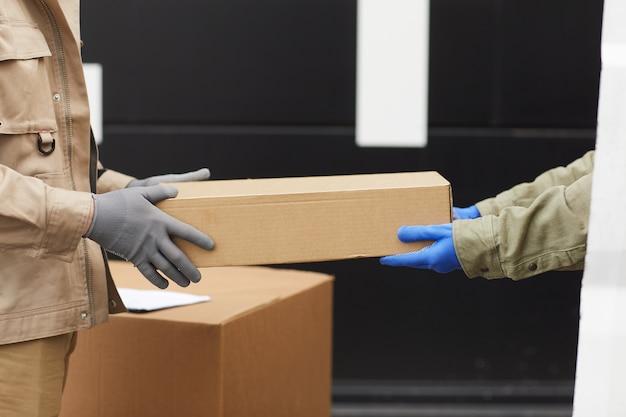 Close-up van handarbeiders in handschoenen die de doos doorgeven aan elkaar die zij met ladingen in magazijn werken