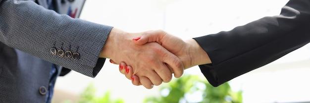 Close-up van handdruk van zakenman en vrouw in pakken in kantoor