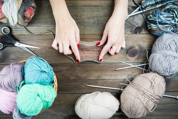 Close-up van handen breien, kleurrijke draden voor handgemaakte winterkleren.