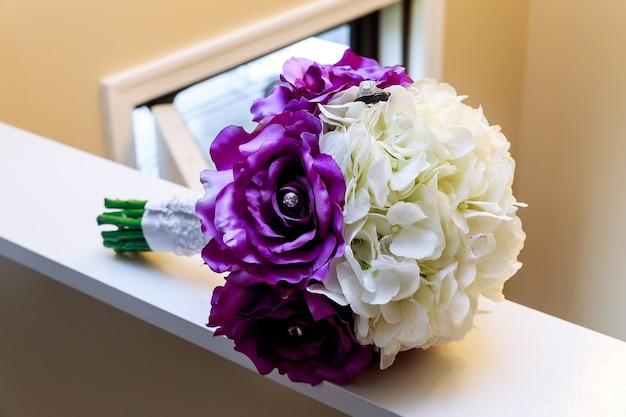 Close-up van handen bruidspaar met trouwringen op aard achtergrond