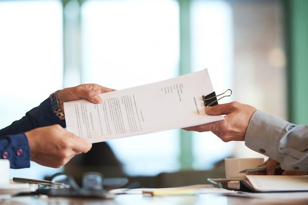 Close-up van handen die het contract doorgeven aan onherkenbare zakenman