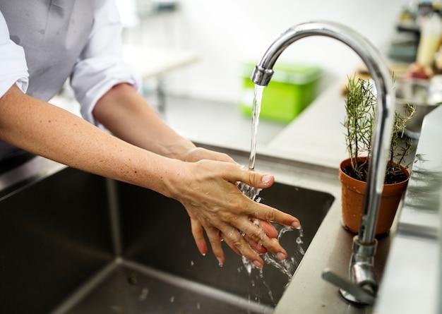 Close-up van handen die in de gootsteen wassen