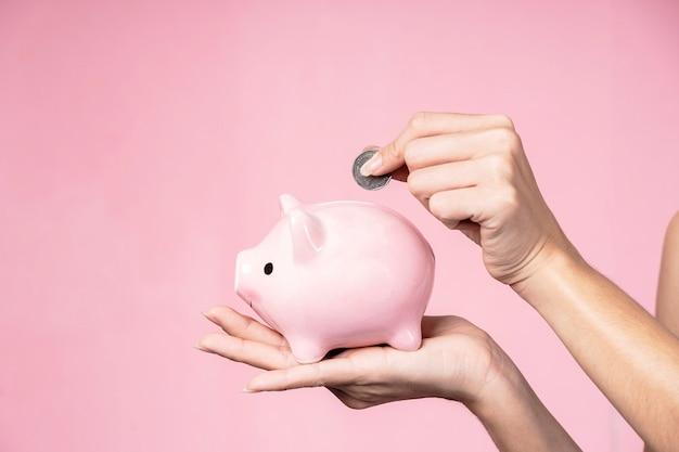 Close-up van handen die muntstuk zetten in een spaarvarken