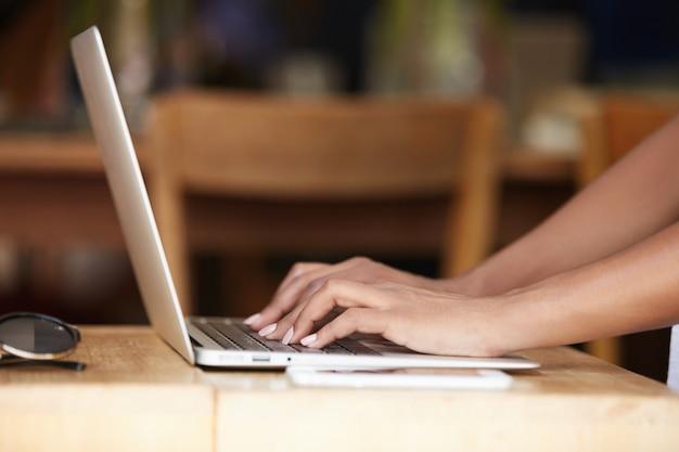 Close-up van handen die op laptop toetsenbord typen