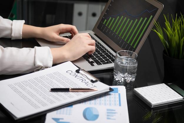 Close-up van handen die op laptop typen die naast contract liggen