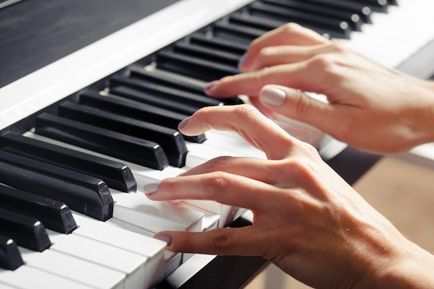 Close-up van handen die piano spelen. muziek en hobby concept