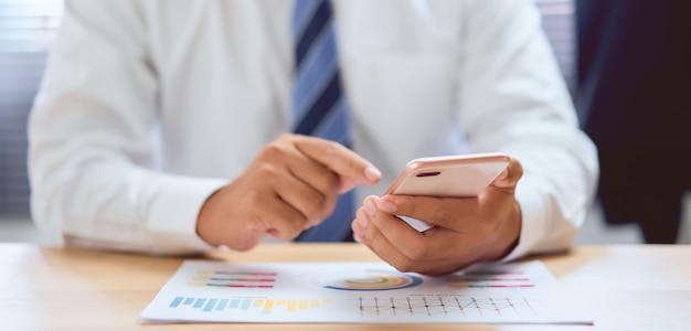 Close-up van handen gebruikend smartphone op houten lijst en typend bericht om banen aan werknemers toe te wijzen.