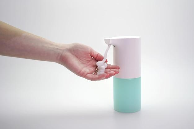 Close-up van handen gedesinfecteerd met een automatische dispenser van schuim, geïsoleerde muur. bescherming tegen virussen en bacteriën