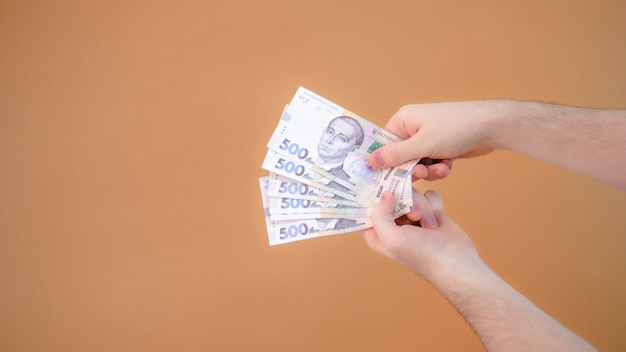 Close-up van handen geven geld op oranje achtergrond