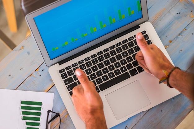 Close-up van handen in dezelfde positie met vinger omhoog kijkend naar de grafiek op de laptop met statistieken - werken op kantoor of thuis