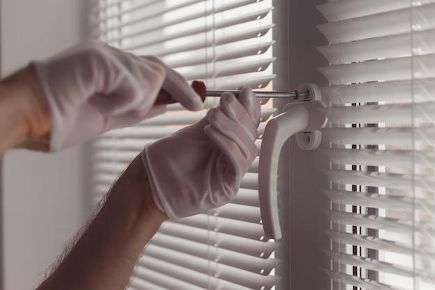Close-up van handen in handschoenen met schroevendraaier, een nieuw handvat installeren.