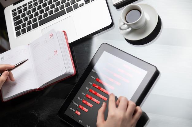 Close-up van handen maken van aantekeningen in agenda naast tabletcomputer