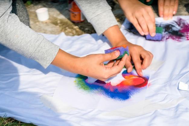 Close-up van handen maken van t-shirt op workshop buiten.