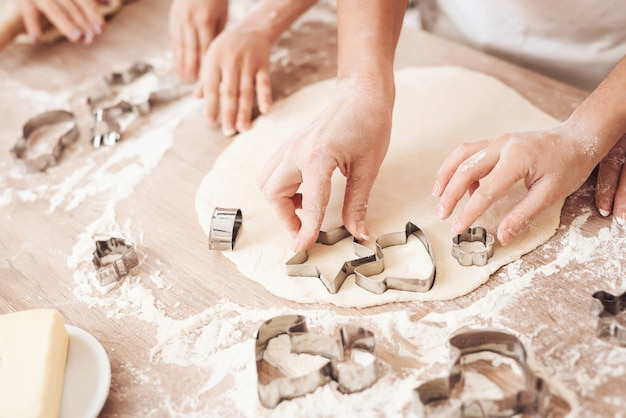 Close up van handen met behulp van cookies cutter op tafel