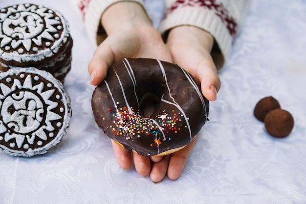 Close-up van handen met chocolade donut met strooi