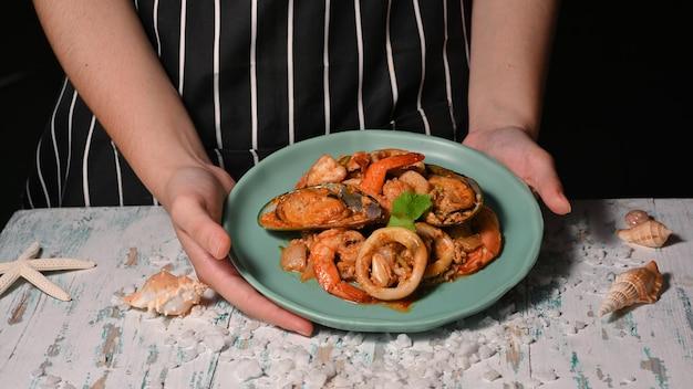 Close-up van handen met een bord thais eten, zeevruchten roergebakken kerriepoeder