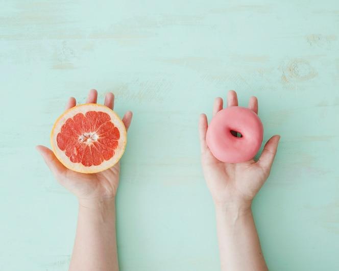 Close-up van handen met grapefruit slice en roze donut over de gestructureerde achtergrond