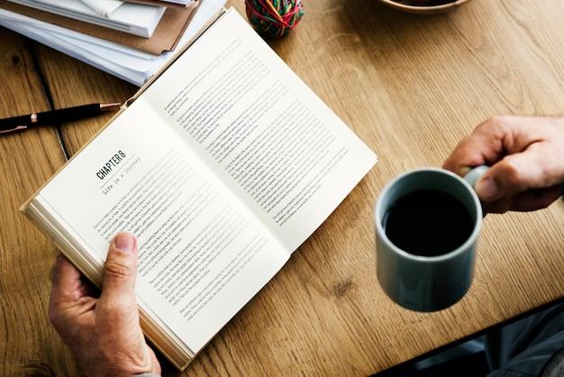 Close-up van handen met open roman en koffiekopje