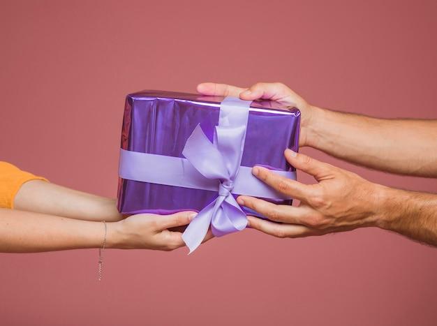 Close-up van handen met paars verpakt geschenkdoos