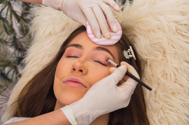 Close-up van handen met professionele make-up artist's handschoenen - portret van een mooie jonge blanke vrouw in een schoonheidssalon.